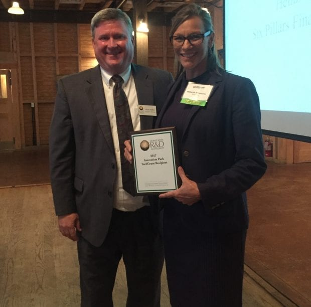 Leon County R&D Executive Director, Ron Miller (right) awarded President of KynderMed, Melanie Simmons (left) with a plaque at Innovation Park's Elevator Pitch Night on May 17th.